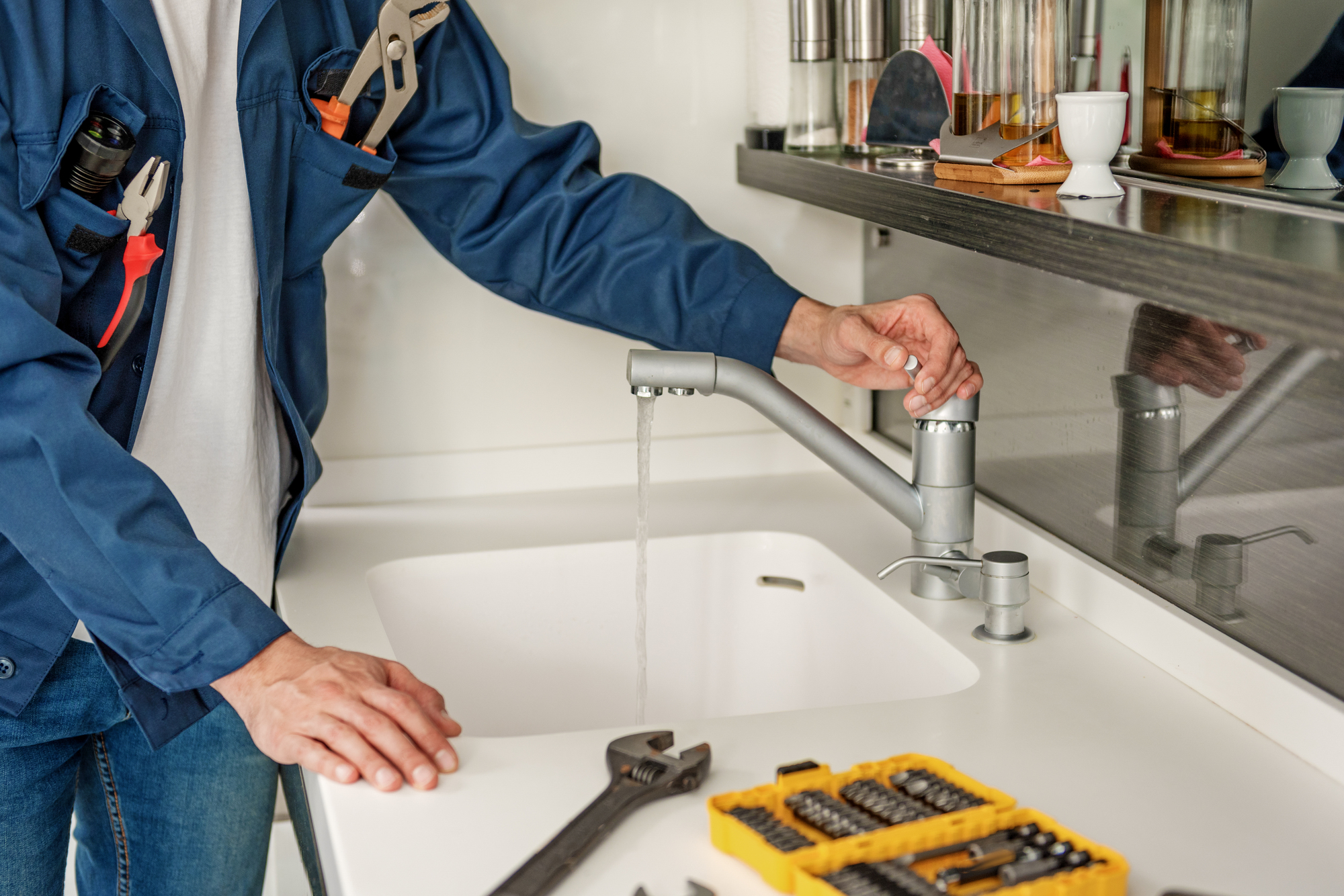 Handyman is opening water tap and checking result. Focus on running liquid. Close up of arms